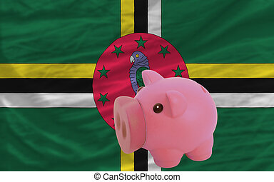 piggy rich bank and national flag of dominica