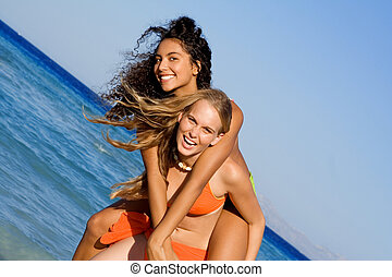 piggyback girls on beach summer vacation or holiday or at spring break