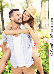 Piggyback in the park - A picture of a romantic couple doing...