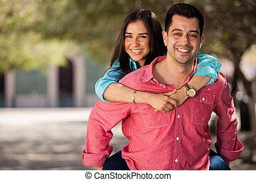Beautiful brunette piggyback riding her boyfriend and having fun outdoors