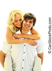 Piggybacking - Happy young teenaged couple enjoying themselves against white