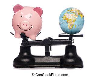 Piggybank and globe on scales