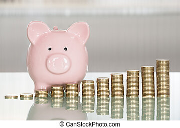Piggybank And Stacked Coins On Desk - Close-up Of Piggybank...