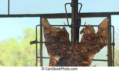 Pigs being roasted - A close up of roasted pigs hung on a...