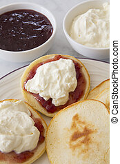 Piklets with Jam and Cream on a Plate with Bowls of Jam and Cream