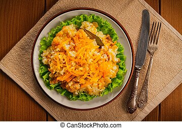 Pilaf in a plate on wooden background, top view