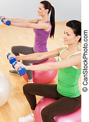 Pilates aerobics women group with stability ball. profile of young girls sitting and holding dumbbells
