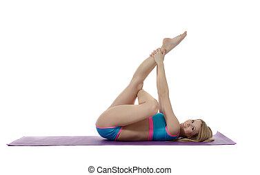 Pilates. Attractive girl training on mat