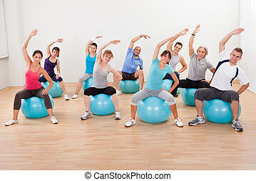 Pilates class exercising in a gym - Large group of diverse...