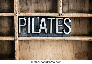 """The word """"PILATES"""" written in vintage metal letterpress type in a wooden drawer with dividers."""