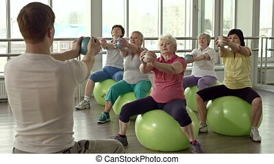 Male instructor with his back to the camera, five ladies sitting on fitball and stretching out hands