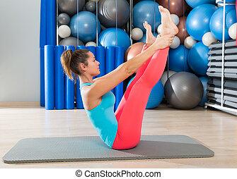 Pilates Open Leg Rocker exercise on mat woman