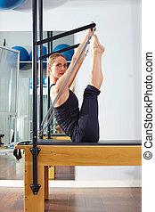 Pilates woman in reformer monki exercise