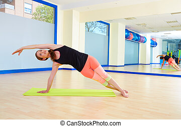 Pilates woman side bend exercise workout at gym