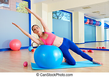Pilates woman side bend fitball exercise