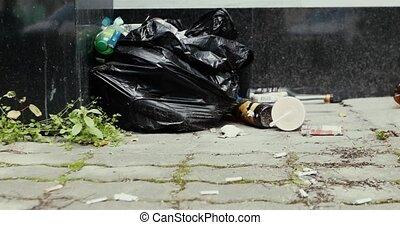 Pile black garbage bag roadside in the city. Abandoned bag...