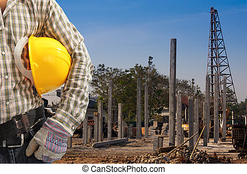 Pile driver works to set precast concrete piles in a construction area