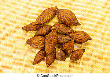 pile fruit brown herring snake fruit Thailand vietnam thin brown rough on a light background