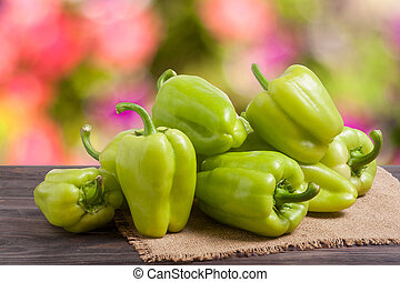 pile green pepper on a wooden table with blurred background