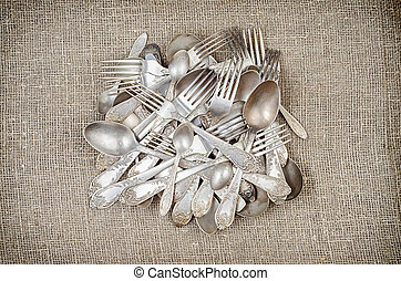 Pile of aged vintage silver cutlery on jute background