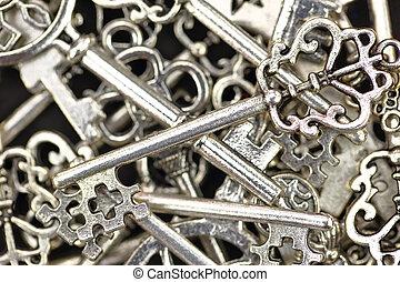 Pile of antique metallic keys closeup background