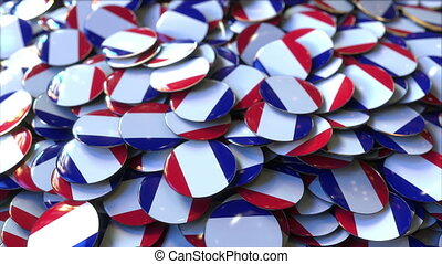 Pile of badges featuring flags of France - Badges featuring...