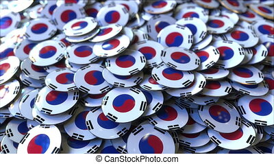 Pile of badges featuring flags of South Korea - Badges...