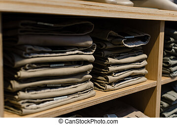 pile of beige jeans on a shop window in the store. Folded jeans are on the shelf. A stack of classic light trousers on a shelf in a store