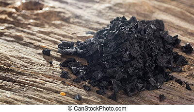 Pile of black salt on wooden table. Closeup view.