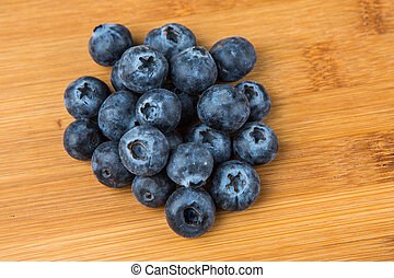 Pile of blueberries isolated on wood background