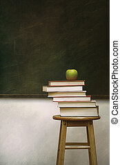 Pile of books and apple on stool
