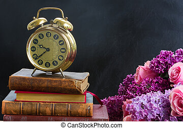 pile of books with clock
