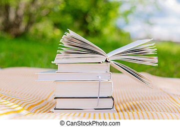 pile of books with one opened book