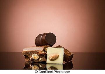 Pile of broken chocolate on table against brown studio...
