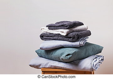 Pile of clean folded home textile items near the white wall.