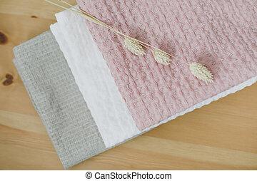 Pile of clean linen cotton towels on kitchen table. Pastel colors. Food photo. Natural linen cotton fabric. Rustic farmhouse style