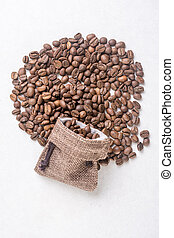 Pile of coffee beans and jute drawstring bag on the white ...