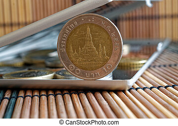 Pile of coins with a front coin denomination of 10 baht in mirror reflect wallet lies on wooden bamboo table background