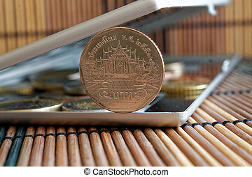 Pile of coins with a front coin denomination of 5 baht in mirror reflect wallet lies on wooden bamboo table background