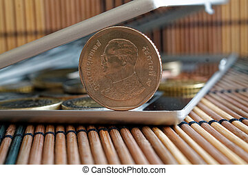 Pile of coins with a front coin denomination of five baht in mirror reflect wallet lies on wooden bamboo table background - back side