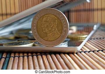 Pile of coins with a front coin denomination of ten baht in mirror reflect wallet lies on wooden bamboo table background - back side