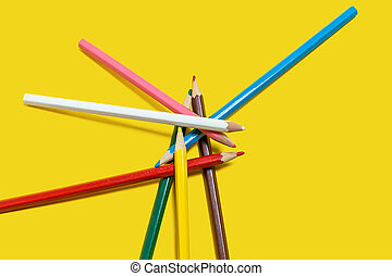 pile of colored pencils on a yellow background