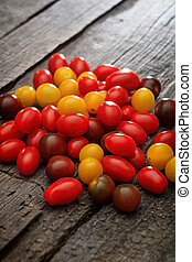 Pile of colorful cherry tomatoes, on wooden surface