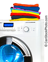 Pile of colorful clothes on the washing machine