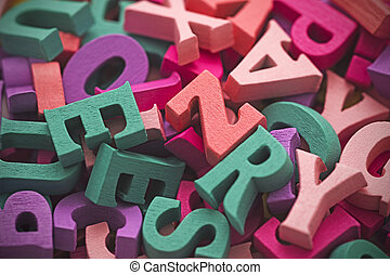Pile of colorful painted wooden letters. Typography background composition.
