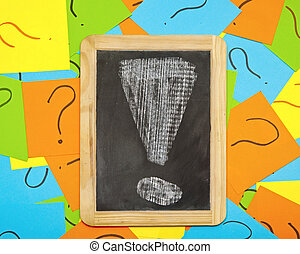 Pile of colorful paper notes with question marks and small blackboard with exclamation mark