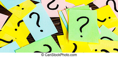 Pile of colorful paper notes with question marks on wooden background. Closeup