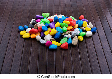 Pile of colorful pebbles on wooden background