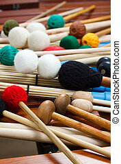 A pile of coloured mallets and a pair of unplugged drum sticks