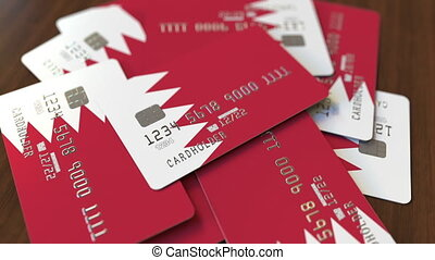 Pile of credit cards with flag of Bahrain. Bahraini banking system conceptual 3D animation